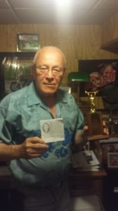 Wayne Gardner holding the 1964 State Champ trophy and a copy of the Obituary of his good friend Wayne Smith.