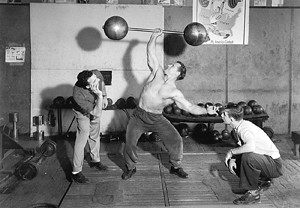 John Grimek performing a one arm overhead lift at the old York Barbell Club.