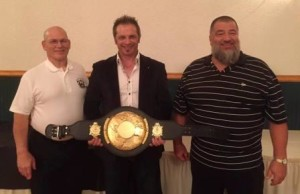 Peter Tryner, of England, being presented the World Championship Belt by meet director Denny Habecker and meet announcer Steve Gardner.