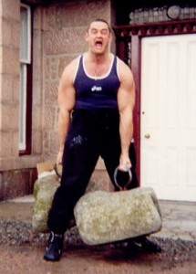 Steve Angell, one of IAWA's strongest ever, displays his own idea of leg training with handled weights on the Dinnie Stones!